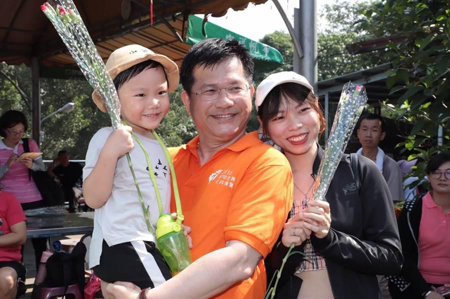 母親節前夕,交通部長林佳龍11日至大坑地區觀音亭向爬山民眾贈康乃馨,與民眾開心合照。(張妍溱翻攝)