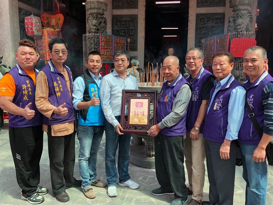 浯島城隍廟主委楊耀芸(右四)致贈捐贈活動衣、帽的在地企業主感謝牌。(李金生攝)