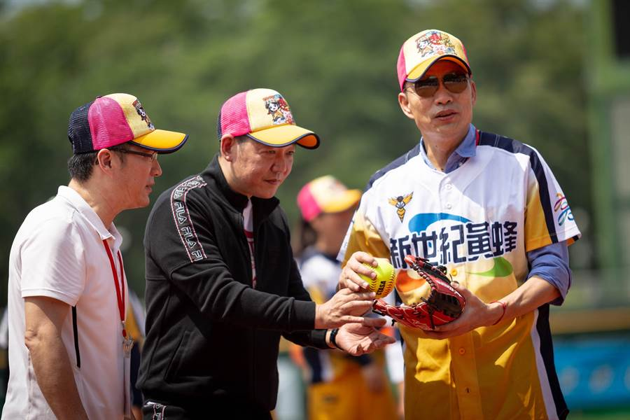開球前,韓國瑜特地詢問正確的壘球投擲法。(袁庭堯攝)