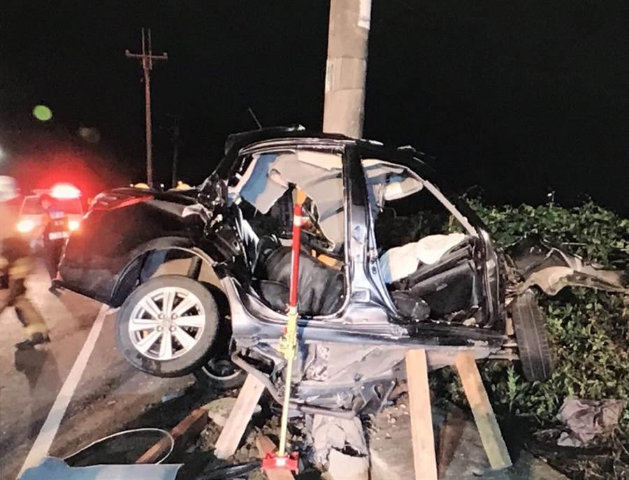 一輛汽車失控自撞致車體扭曲「包」住電線桿。(洪榮志翻攝)
