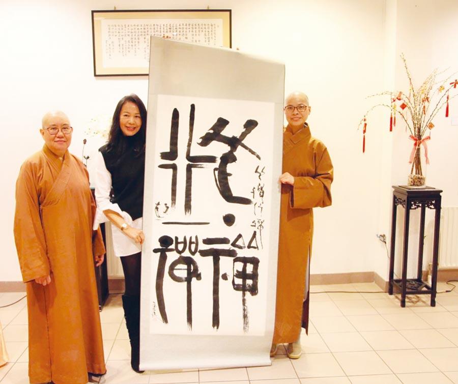 藝術家陳玉庭(中)將即席揮毫的作品「行一禪,坐一禪」獻給荷華寺,由滿容法師(左)及妙益法師(右)代表接受。圖/陳玉庭提供
