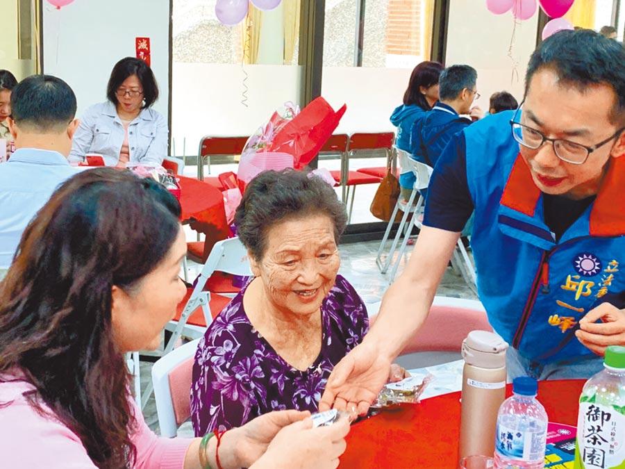 邱一峰(右)積極爭取國民黨第二選區立委參選的資格,以喜憨兒烘焙坊的手工餅乾,取代常見的康乃馨,作公益也送愛心。(邱一峰團隊提供)