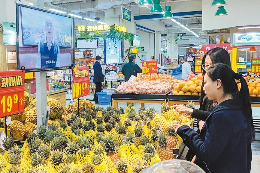 4月2日,北京市民在一家大型超市選購來自台灣的鳳梨。(中新社)