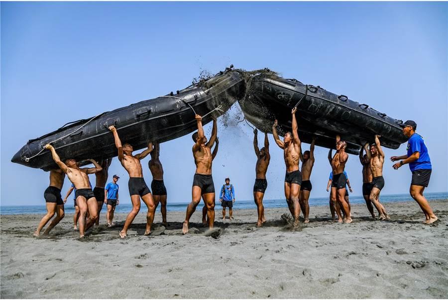 海軍陸戰隊兩棲偵搜專長班第148期學員各高舉重達146公斤的橡皮艇,全力朝對方艇身衝撞、壓制。(國防部提供)