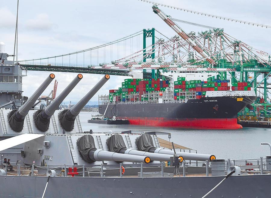 美國總統川普下令將對3250億美元所有大陸商品加稅,雙方對峙情勢升高。圖為一艘貨輪在加州港灣卸貨,美國超級戰艦正好停靠港邊。(法新社)