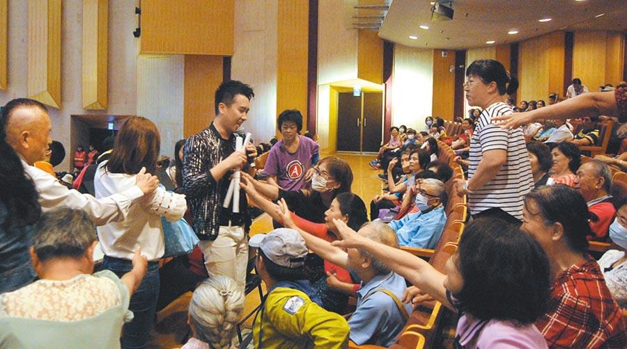 旺旺文教基金會向嘉義市志工致敬演唱會,歌手沈建豪贈送海報,觀眾熱情索取。(廖素慧攝)