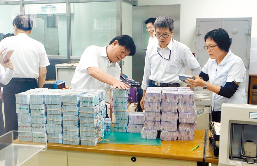 朱國榮2016年因案起訴,台北地院裁定4億元交保。圖為台灣銀行行員清點朱的交保金。(本報資料照片)