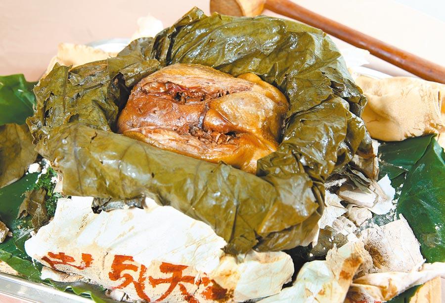 富貴土雞又稱叫化雞,土雞和多種食材以文火煨烤6小時後,食用時才破泥開封。(粘耿豪攝)