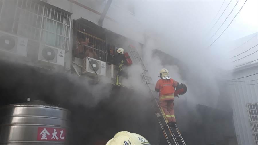 工廠火警現場濃煙密佈,三名移工受困工廠二樓陽台,消防人員架梯上去救人。(謝瓊雲翻攝)