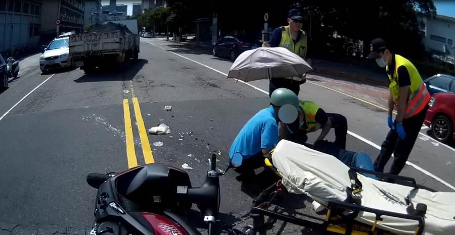 三分局合作所員警巡邏遇車禍,立即下車幫自摔的林女拿傘遮陽。(馮惠宜翻攝)