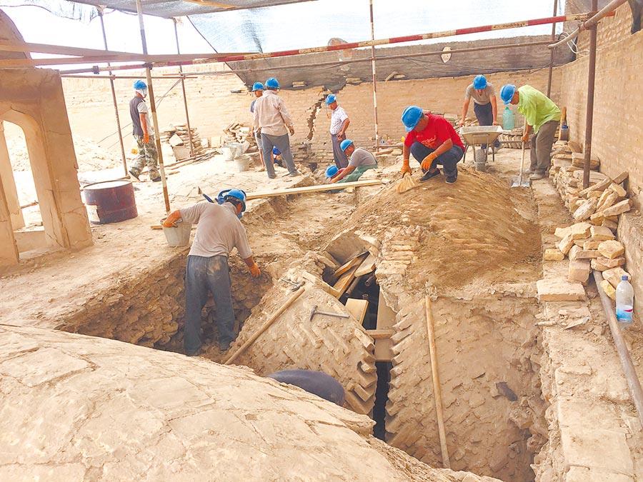2018年6月21日,中烏文物修復人員,在希瓦古城經學院穹頂上方加固施工。(新華社/中國文化遺產研究院提供)