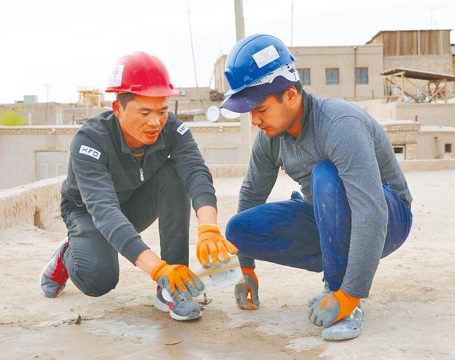 4月22日,在烏茲別克希瓦古城,中方文物修復人員(左)在指導烏方人員修復清真寺屋頂。(新華社)