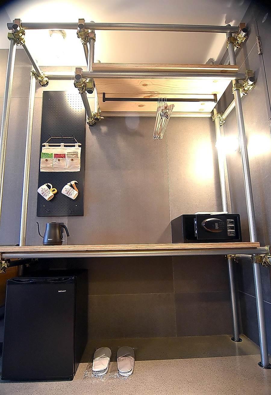 捷絲旅三重館客房內的衣櫃與置物櫃,是用架設演唱會舞台的金屬鋼管桁架設計,簡約中帶著工業風時尚感。(圖/姚舜)
