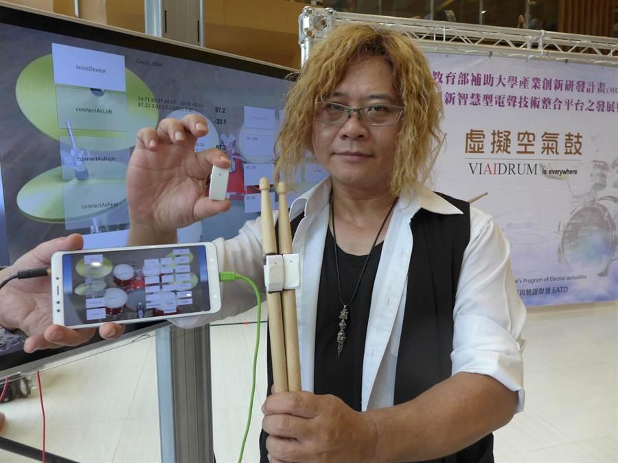 逢甲大學電聲團隊研發成員黃興真拿著綁有「IST感測器」的鼓棒,強調就是這小小的感測器能將樂器虛擬化。(林欣儀攝)