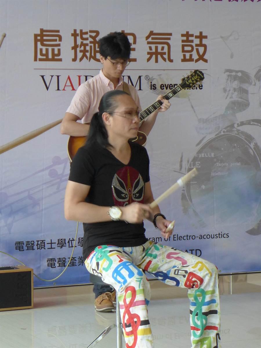 專業鼓手陳世南拿著綁有「IST感測器」的鼓棒(空氣鼓),對著空中敲打。(林欣儀攝)