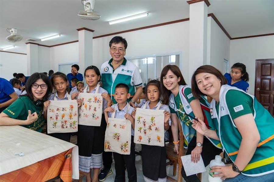(第一銀行志工團們與當地弱勢孩童一起DIY「蝶谷巴特環保袋」體驗手作樂趣,創造獨一無二專屬的作品。 圖:第一銀行提供)