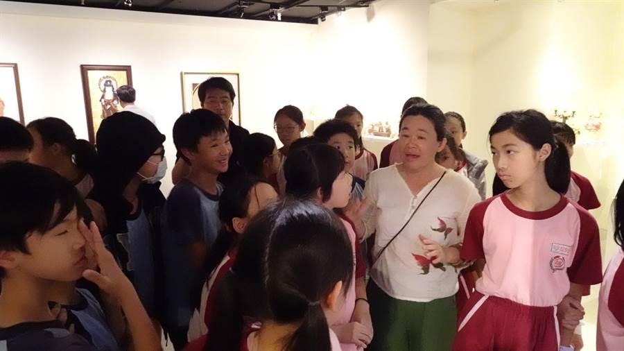 布藝創作者廖芳英(前右二)為永平國小5年級美術班學童導覽「布施自在~廖芳英布貼聖像畫作品展」。(世界宗教博物館提供)