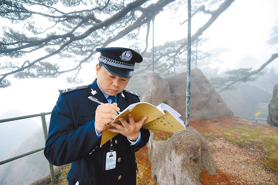 2013年2月27日,迎客松守护人胡晓春在填写工作日志。(新华社)