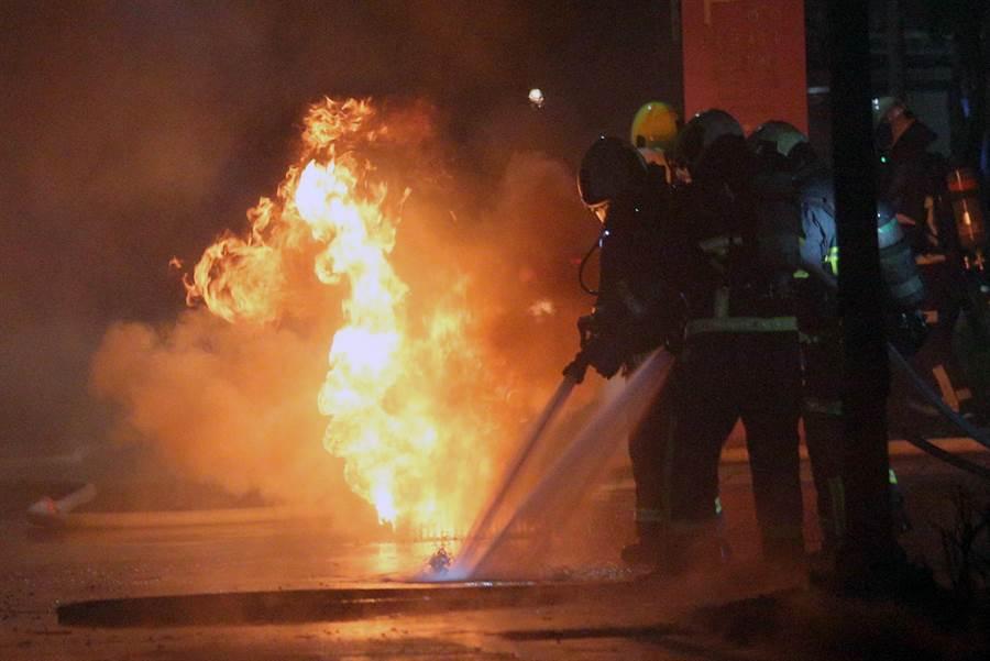 發電機用油流入水溝,火勢隨著水溝延燒,不時冒出火舌,現場濃煙密布。(黃世麒攝)