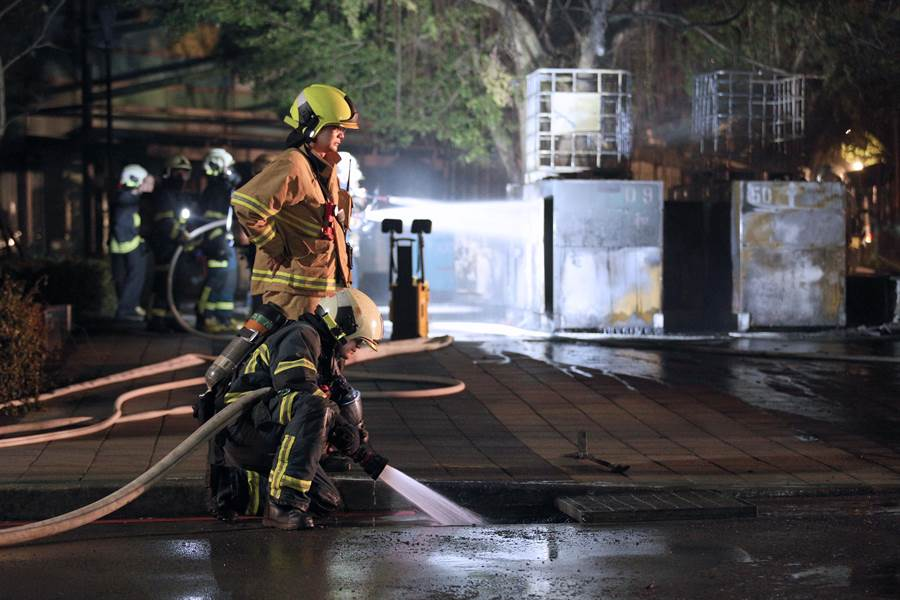消防員朝水溝內射水降溫。(黃世麒攝)