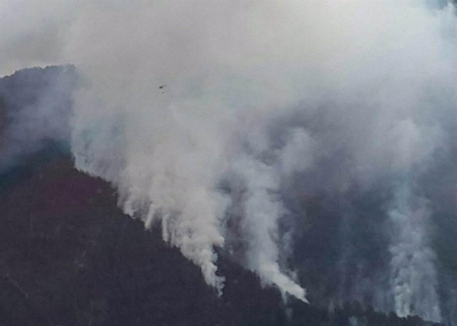 相片左上方的小黑點,就是吊掛水袋滅火的空勤總隊直升機。〈消防局提供〉