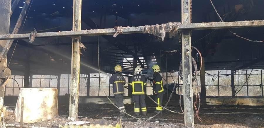 消防人員撲滅屋頂上殘火,現場殘留許多雞隻毛屑。(巫靜婷翻攝)