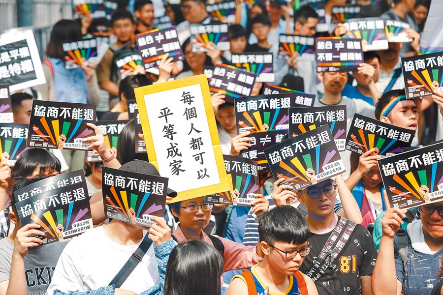 立法院14日針對同婚專法進行逐條朝野協商,挺同團體成員在場外召開記者會,持標語看板高喊「結合不是結婚,台灣婚姻不要一國兩制」口號,力挺政院版同婚草案。(郭吉銓攝)