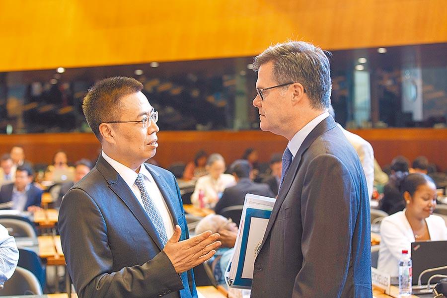 2018年7月26日,中國駐世貿組織代表張向晨(左)駁斥美國對中國經濟模式的指責,並與美方代表進行面對面溝通。(新華社)