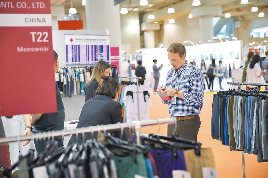 2018年7月24日,第十九屆中國紡織品服裝貿易展覽會在紐約開幕,美國客商在一家江蘇成衣廠展台記錄價格。(新華社)