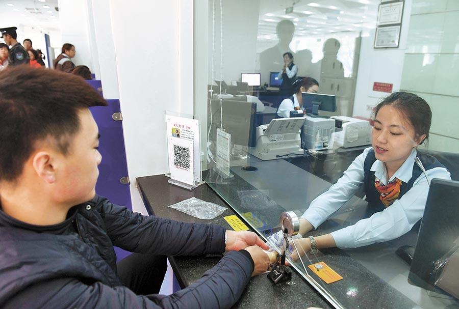 中國建設銀行的行員為客戶服務。(新華社)