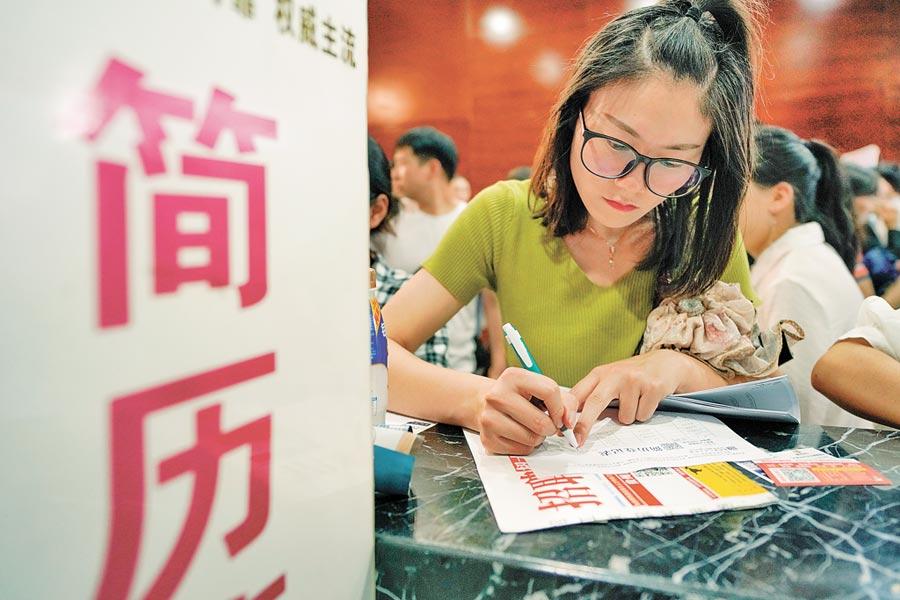 2019年各省市最低工資排行榜出爐,圖為求職者在人才博覽會上填寫履歷。(中新社)