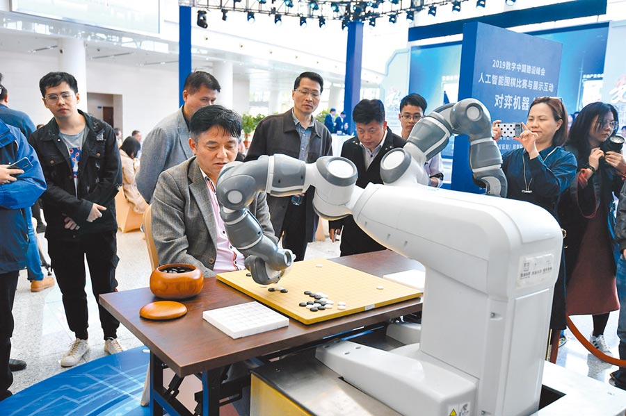 5月7日,福州一名圍棋愛好者與機器人下圍棋,吸引觀眾圍觀。(中新社)