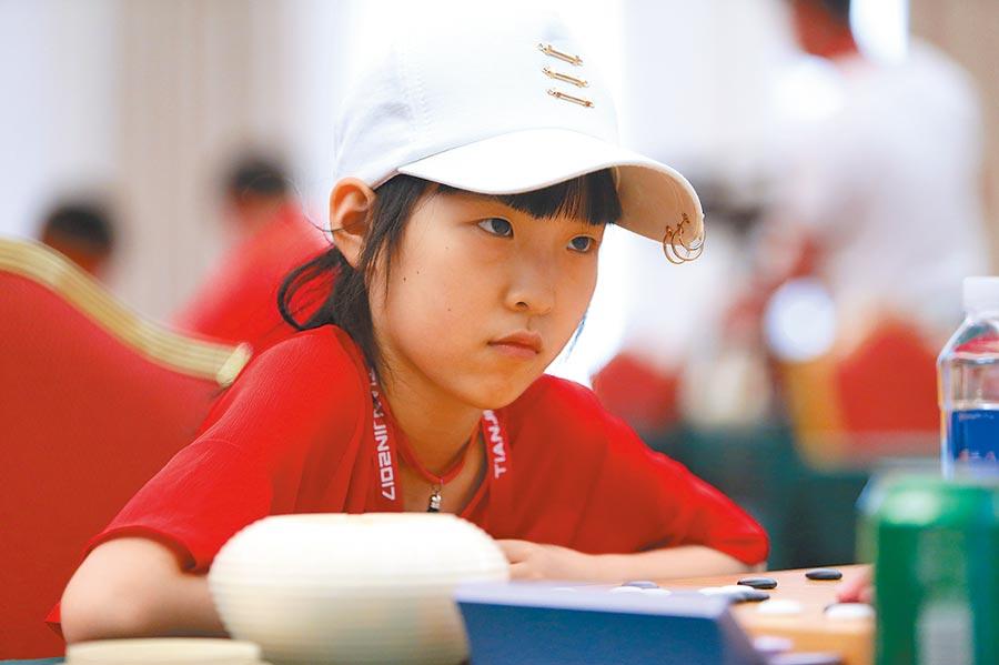 2017年7月5日,當時年僅10歲的江蘇隊選手吳依銘在圍棋業餘組女子個人賽中思考。(新華社)