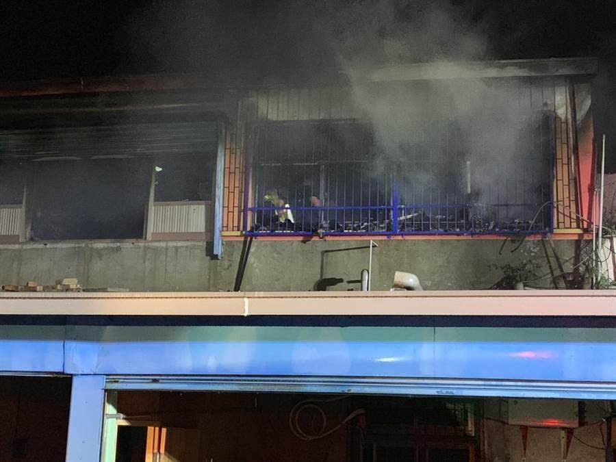 暗夜惡火襲民宅,濃煙伴隨火舌從鐵窗竄出。(巫靜婷翻攝)