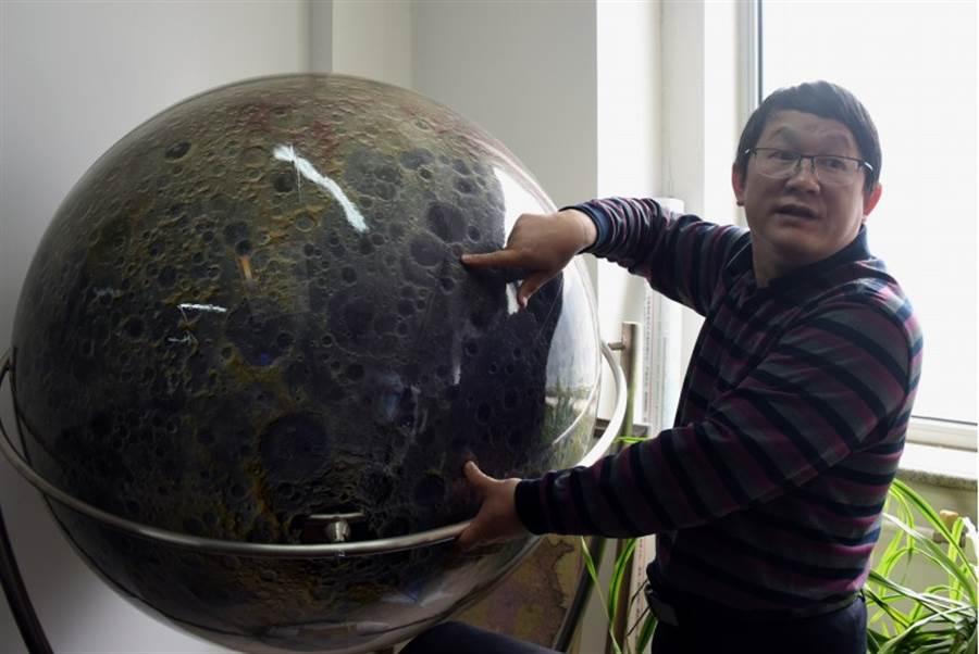 中國科學院國家天文台5月16日說,由李春來領導的研究團隊利用嫦娥4號就位光譜探測數據,發現並證明月背南極-艾托肯盆地存在以橄欖石和低鈣輝石為主的月球深部物質,這為解答月幔物質組成提供了直接證據。圖為論文發表前夕,李春來利用月球儀向媒體介紹嫦娥4號在月背著陸的位置。(中新社)