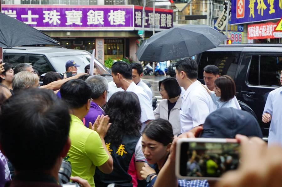 蔡英文總統車隊抵達慈濟宮時,正好下大雨,支持者熱情不減,爭相向前握手。(王文吉攝)