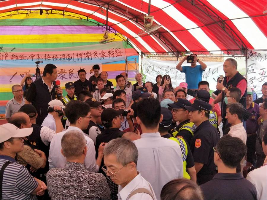台中港務分公司總工程司朱志光堅持進行擴建環評說明會,遭多位里長等人包圍,現場一團混亂。(陳淑娥攝)