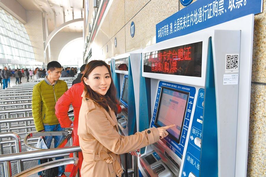 來自高雄的台青朱德容,體驗以居住證購買高鐵票的方便和快捷。圖為她在自助取票。(中新社)