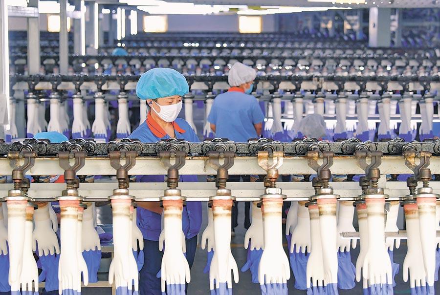 大陸經濟可望持續看好。圖為5月14日,工人在河北灤南縣一家醫療用品企業的手套生產線上工作。(新華社)