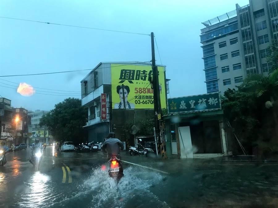 新竹地區大雨不斷,不少路段出現積水,上班族冒雨通勤。(莊旻靜攝)