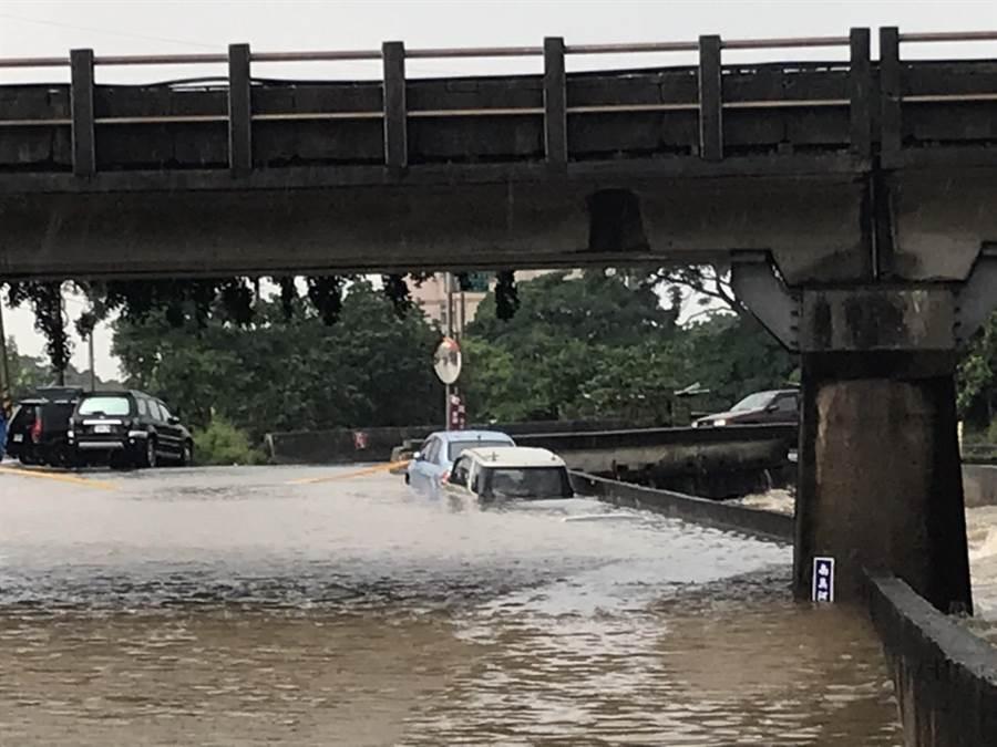 湖口鄉東興橋下溪水幾乎與一旁路面平高,停放四輛車均泡水,其中兩輛慘遭滅頂。(莊旻靜攝)