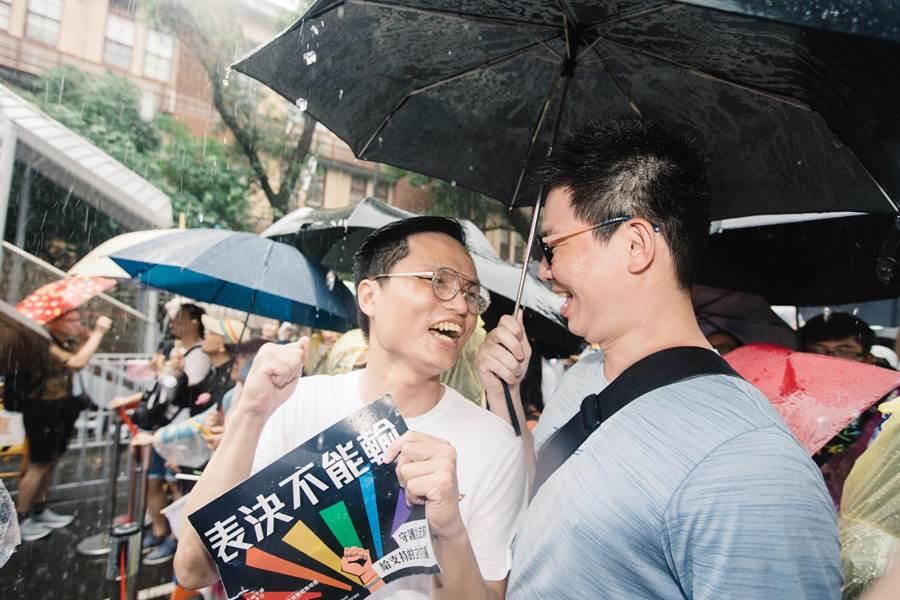 同婚法案三讀通過,雨中仍在院外守候的支持群眾獲知後難掩振奮。(郭吉銓攝)