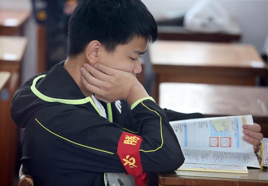 國中教育會考18日登場,一位考生一大早即到考場內復習,手上纏著「必勝」布條展現決心。(姚志平攝)