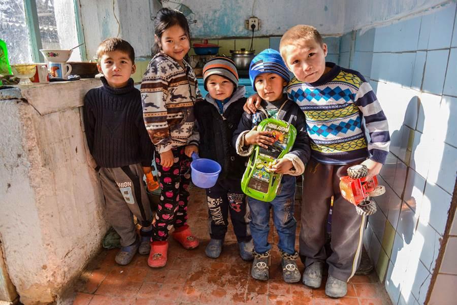 吉爾吉斯冬天常降到攝氏零下20至30度,對沒有暖氣設備的家庭而言,廚房是最溫暖的空間,圖為小朋友擠在裡面避寒。(圖/家扶基金會提供)