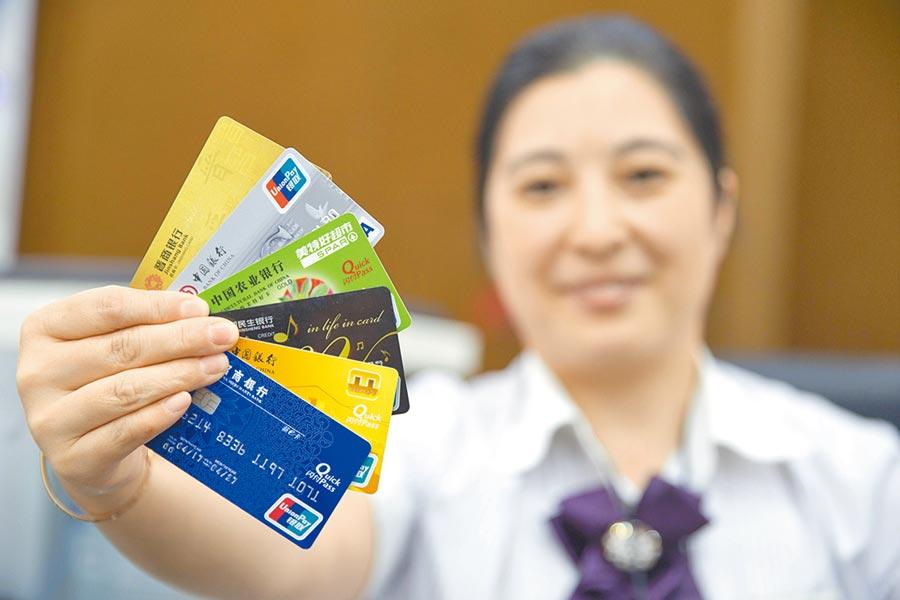 山西太原一銀行工作人員正在展示信用卡。(中新社)