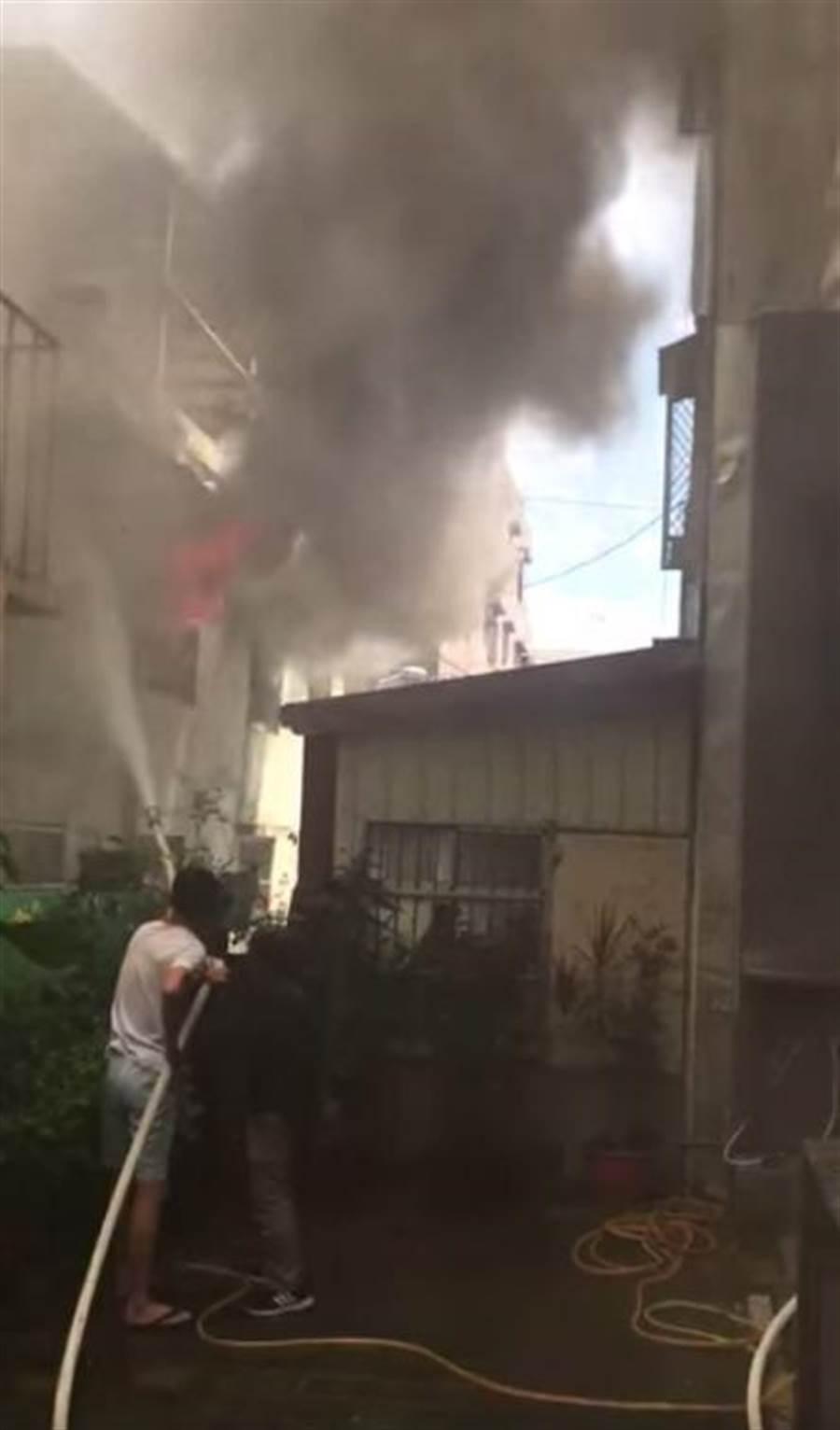 失火住宅後方的東華浸信會教友,發現立即抱水帶協助滅火。(許家寧翻攝)