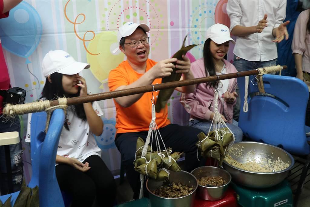 適逢端午節將至,華夏科技大學20日舉辦「南勢學園老少共學,發現文化之美」活動,華夏科技大學校長陳錫圭(中)與越南籍交換學生一起包粽子。(葉書宏翻攝)