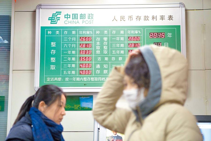 山西太原某儲蓄所內,民眾從人民幣存款利率表前走過。(中新社資料照片)