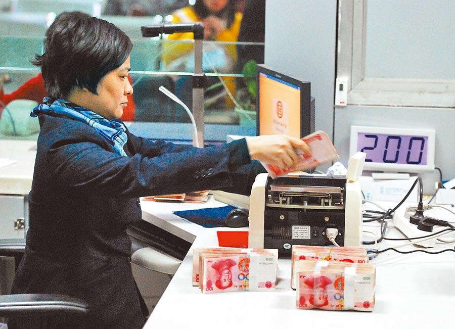 中國工商銀行某分行的工作人員在清點人民幣。(新華社資料照片)