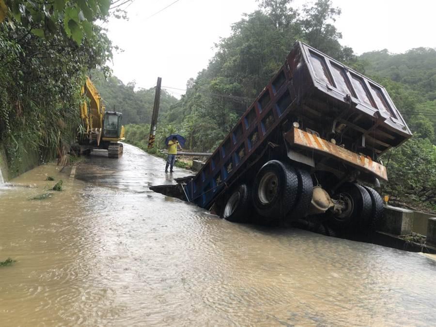 連日大雨,埔里鎮向善路地基疑似遭到暴漲溪水淘空,砂石車陷落洞內。(圖/南投縣政府提供)